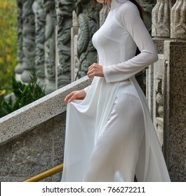 An Asian woman in Vietnamese traditional dress (called Ao Dai) at Chinese pagoda in Hong Kong.