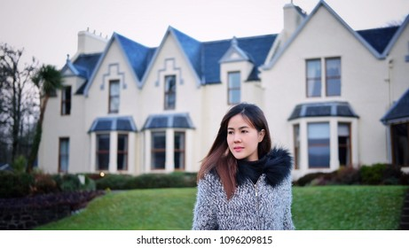 Asian woman with vintage hotel building  in background at Portree, Isle of Skye, Highland, United kingdom