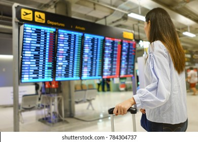 Asian woman waiting flight with a luggage  looking at departures board in airport terminal, Travaling concept