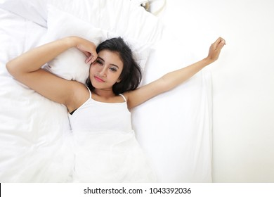 asian woman wake up happy. Beautiful woman waking up in her bed in the bedroom, she is stretching and smiling.