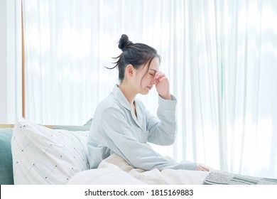 Asian woman waking up with headaches