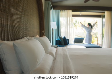 Asian woman waking up in the morning taking some rest relaxing in comfort hotel room. Focus on pillow