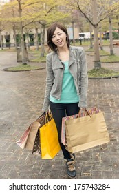 Asian woman walk and hold shopping bags at street after raining in Taipei, Taiwan,  Asia.