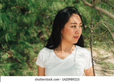 Asian woman walking chill under the shade of pine tree.