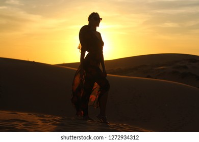Asian woman walking and enjoy sand dune. Girl's silhouette on a sunset.