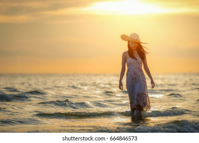 Asian woman walking on the beach at sunset.