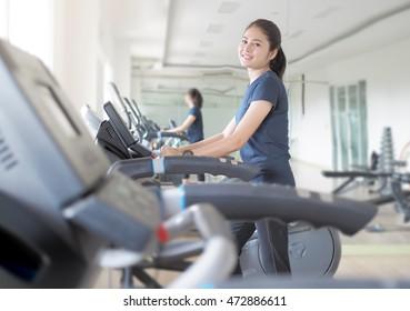 Asian woman walking,  running on treadmill gym workout.