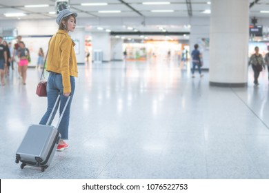 asian woman  walking with suitcase on the airport terminal,travel concept