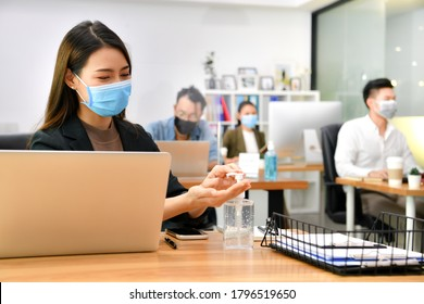 Asian woman washing hands sanitizer gel and wearing face mask working in new normal office and doing social distancing during corona virus covid-19 pandemic
