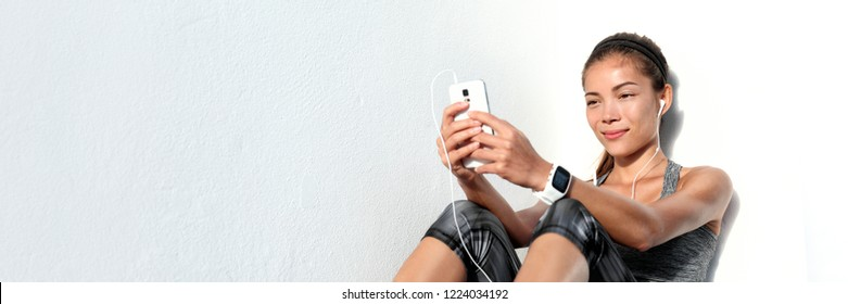 Asian woman watching online fitness videos using mobile phone listening to music with earphones and smartwatch. Technology banner panorama. Active lifestyle. Sports wearable tech device.