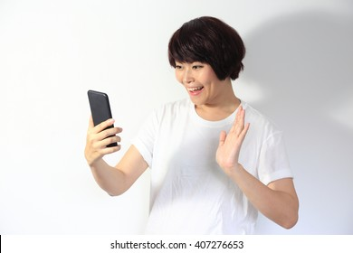 The Asian woman waving hand with mobile phone.