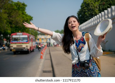 Asian woman waving her hands to get on the tuk-tuk which is kind of local transportation in Bangkok Thailand.