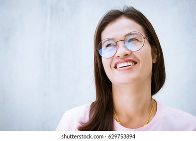 Asian woman wear eyeglasses looking upward and smiles with happiness