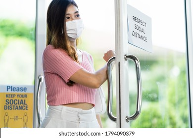 Asian woman wear face mask entering shop or restaurant, open entrance door with forearm or elbow. Hygienic new normal lifestyle and social distancing concept