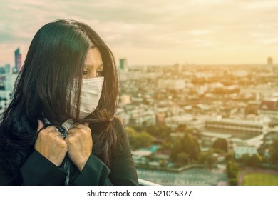 Asian woman wear protective face mask in pollution city and background of the city and leave space for adding your content. Concept of air pollution (vintage color tone, lens blur effect)