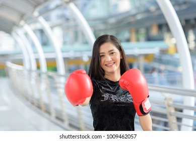 Asian woman wear red glove of boxing while her feeling happy time