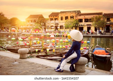 Asian woman is wearing Ao Dai traditional Vietnamese dress and traveling at Hoi An old town in Vietnam.