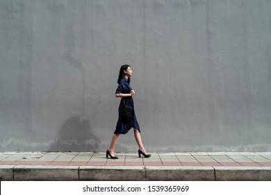 Asian woman wearing blue dress walking on high heel on street.
