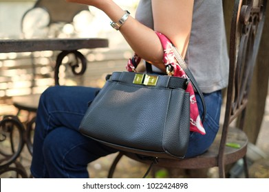 A asian woman wearing blue jeans and watch is shoulder a black leather bag was sitting on the chair in the garden with tree, wall, and sunlight bokeh background.