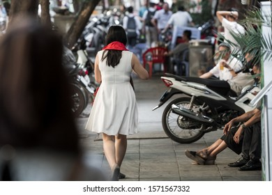 An asian woman wearing a bright red scarf that was bought as a present walking through the streets of Hanoi, Vietnam, Asia