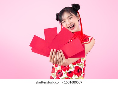 Asian woman wearing cheongsam traditional red dress for Chinese new year day 2020 holding red envelopes isolated on pink background