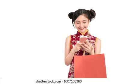 Asian woman wearing chinese dress with mobile smartphone shopping online technology holding shopping bag cheongsam,qipao concept on white isolated background