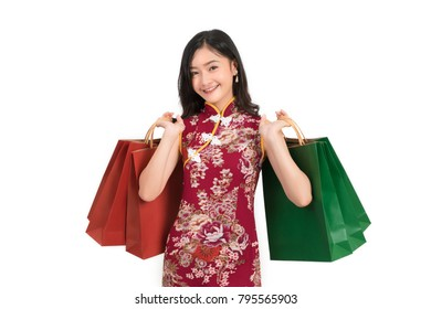 Asian woman wearing chinese dress hold shopping bag cheongsam,qipao smile in chinese new year on white isolated background