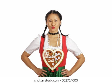 Asian woman wearing Dirndl holding gingerbread heart
