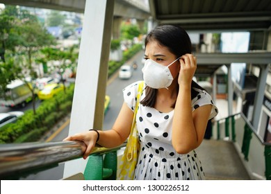 Asian woman wearing disposable mask (respirator) for pollution and personal protection on city background. Safety device that covers the nose and mouth, helps protect from breathing in some hazardous.