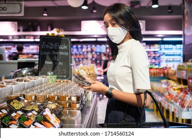 Asian woman wearing face mask protection from coronavirus in market store