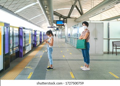 Asian woman wearing face mask and using phone and keep distance to other people while waiting subway in empty subway platform during coronavirus outbreak. social distancing, new normal concepts
