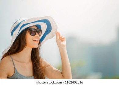 Asian woman wearing fashion straw beach hat for skin care sun protection. Face skincare beauty concept. Beautiful adult girl portrait on summer vacation travel.