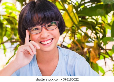 Asian woman wearing glasses posing smiling happily in the summer.