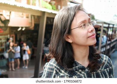 Asian woman wearing glasses and smiling on blur background