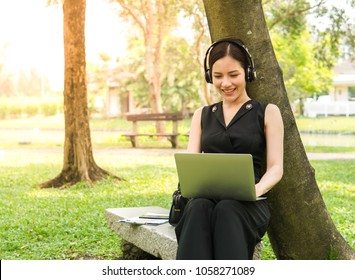 Asian woman wearing a headphone listen to the music with laptop.