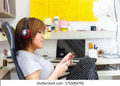 asian woman wearing headphone using mobile phone work at home.