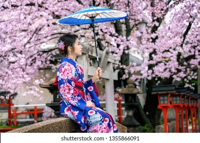 Asian woman wearing japanese traditional kimono and cherry blossom in spring, Kyoto temple in Japan.