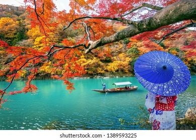 Asian woman wearing japanese traditional kimono at Arashiyama in autumn season along the river in Kyoto, Japan.