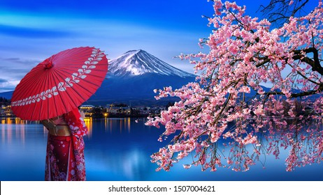 Asian woman wearing japanese traditional kimono at Fuji mountain and cherry blossom, Kawaguchiko lake in Japan.