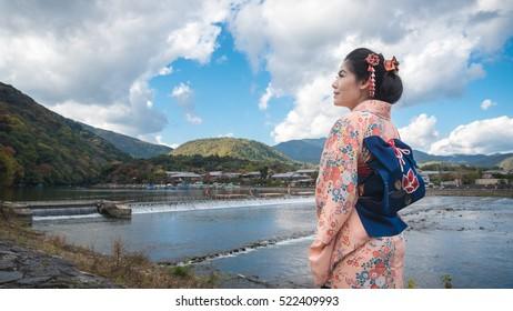 Asian woman wearing Kimono (Japanese traditional costume) walking in Arashiyama during autumn.