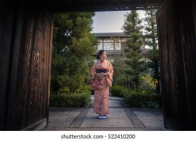 Asian woman wearing Kimono (Japanese traditional costume) standing in Japanese traditional house during autumn.
