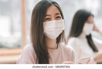 Asian woman wearing mask to protect virus while using mobile phone in coffee shop. New Normal and Social distancing Concept. - Shutterstock ID 1896907456