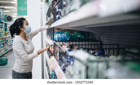 Asian woman wearing a mask shopping in the supermarket during new normal change after coronavirus or post covid-19 outbreak pandemic situation
