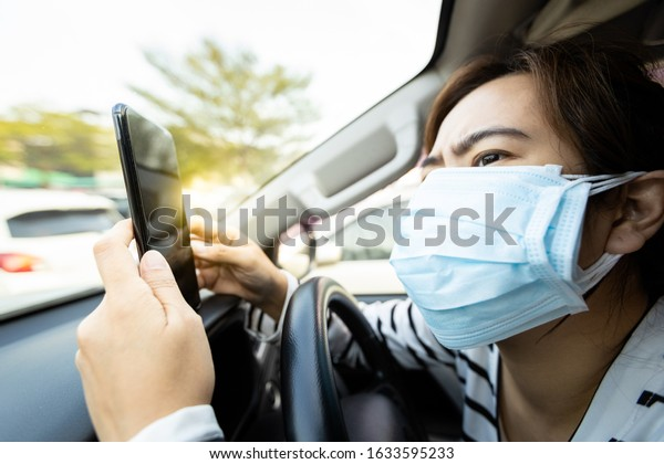 Asian woman wearing medical face mask of many layers,worried people check information or search for news from the phone about epidemic,spread of germ,Coronavirus,Covid-19,Wuhan coronavirus 2019-nCoV