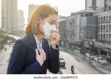 Asian woman wearing the N95 Respiratory Protection Mask against PM2.5 air pollution and headache Suffocate
