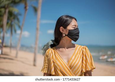 Mujer asiática con mascarilla protectora en la playa, estilo de vida nuevo después de la pandemia del Coronavirus.