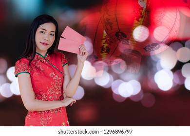 asian woman wearing red traditional dress holding red pocket with the chinese new year festival background with lanterns having letter meaning goodluck and success