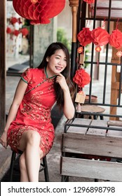 asian woman wearing red traditional dress in chinese new year festival background with lanterns having letter meaning goodluck and success