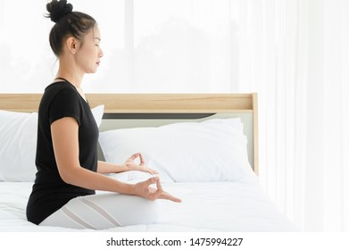 Asian woman wearing sportswear  practicing meditation yoga on bed in white bedroom, doing Accomplished Pose or Siddhasana asana in the morning. Healthcare concept of calm and relax with Yoga posture e