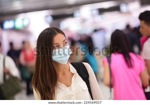 Asian woman wearing surgical face mask against infectious disease protection against cold common flu. Young tourist commuter girl walking in  airport public area.